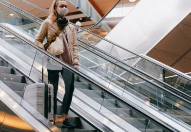 woman with a face mask standing on an escalator