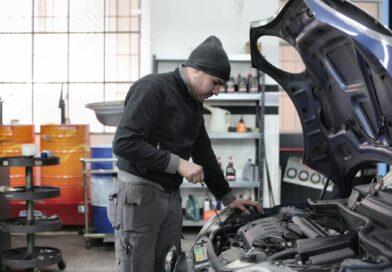 photo of man inspecting car engine